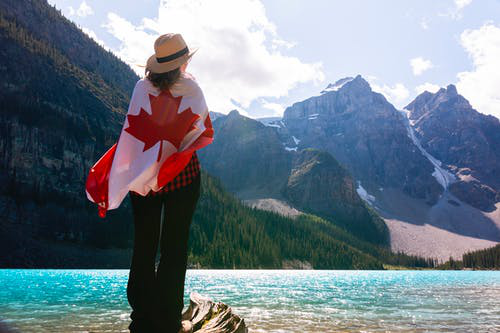 A girl standing with a Canadian flag on her back and a great view in the front.